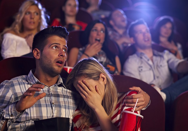 Young couple watching horror movie in cinema, girl turning her head away with fear..