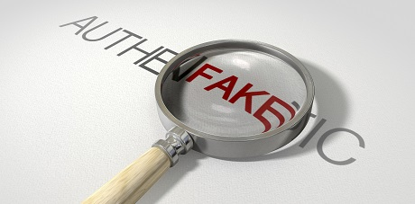 A concept image of a magnifying glass with a wooden handle on a textured white surface showing the word authentic but magnifying the word fake resembling counterfeitting